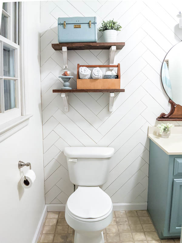 Reclaimed wood shelves with diy white wood shelf brackets against wood accent wall over toilet in small bathroom.