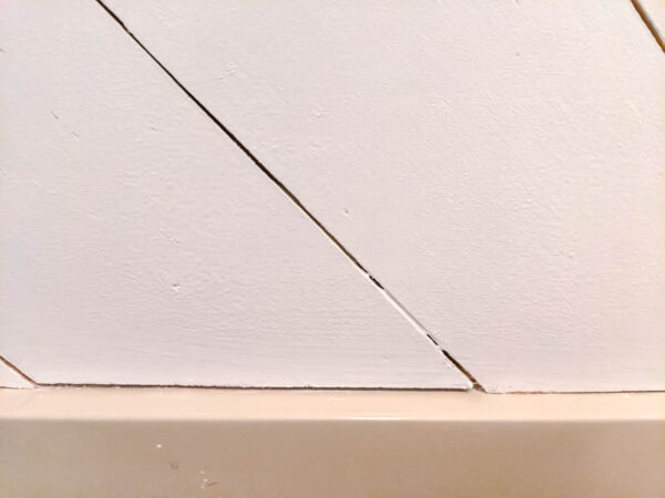 close up of space between two boards with paint drips
