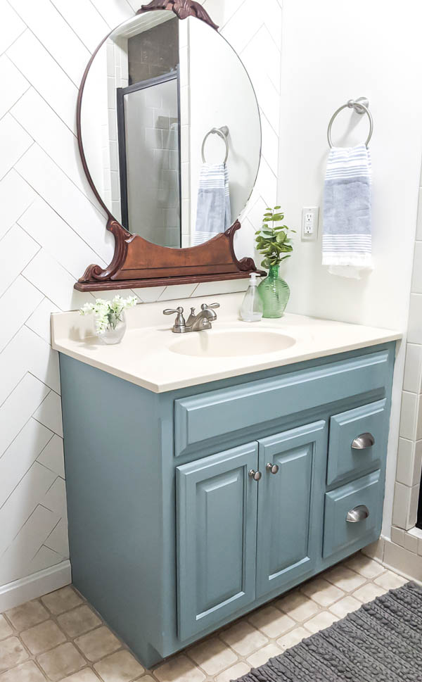 Bathroom vanity painted General Finishes Persian Blue with nickel bin pulls and a vintage round mirror