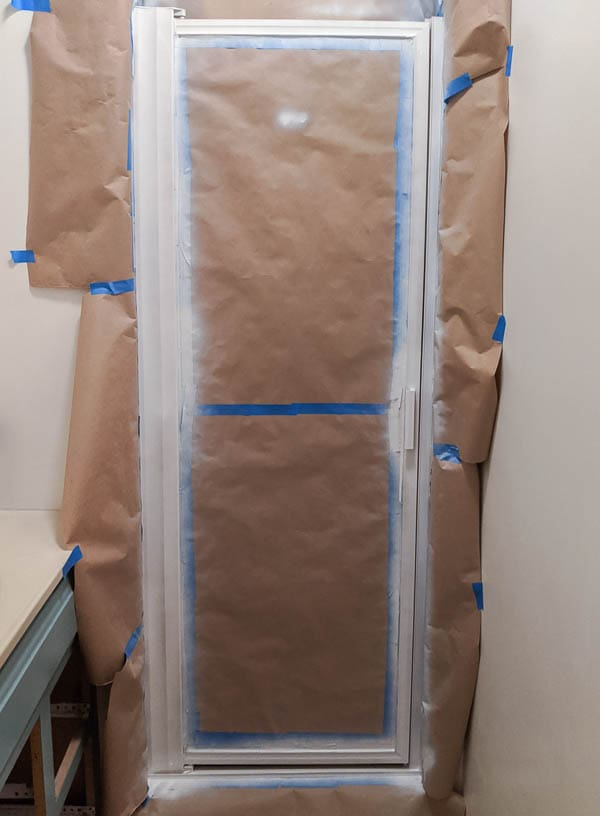 shower door frame surrounded by painters tape and primed with white spray primer