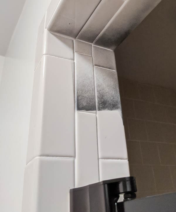 shower tiles with overspray from black spray paint