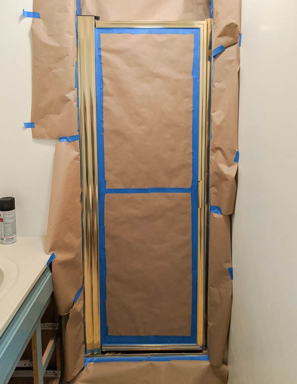 gold shower door surrounded by painter's tape and brown butcher paper to protect the walls from overspray