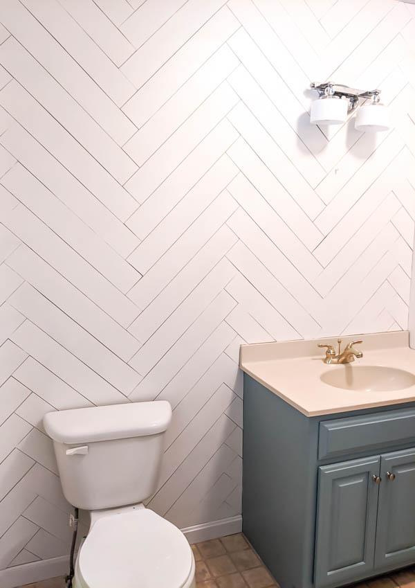 bathroom with white herringbone wood wall, blue vanity, and toilet.