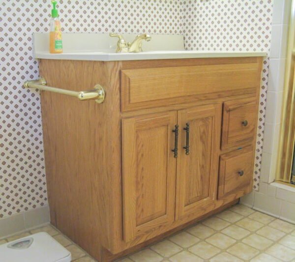 basic oak bathroom vanity with shiny gold faucet and old brass hardware