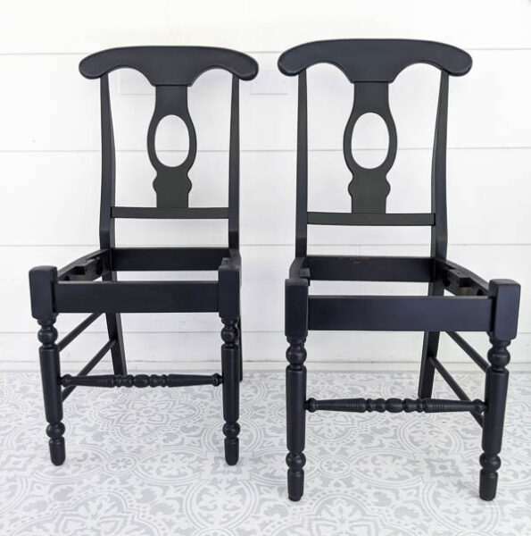 two wooden chairs with the seats removed painted black