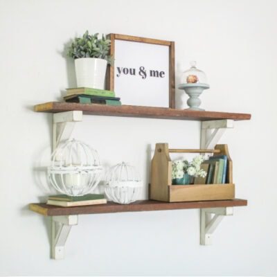 diy wood shelves with white wood shelf brackets decorated with a sign, plants, books, and other nick knacks