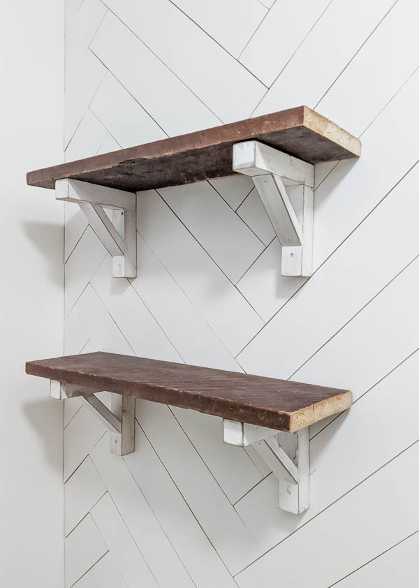 Reclaimed wood shelves with white diy wood brackets hanging on a white herringbone wood wall.