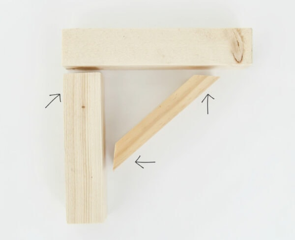 DIY wood shelf brackets with arrows pointing to the three spots where finishing nails are used to attach them.
