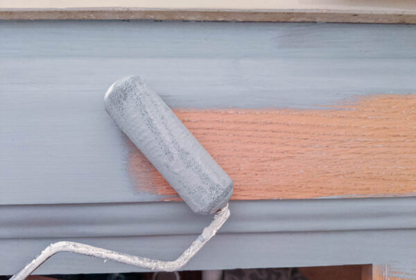 using a small foam roller to paint a bathroom cabinet light blue