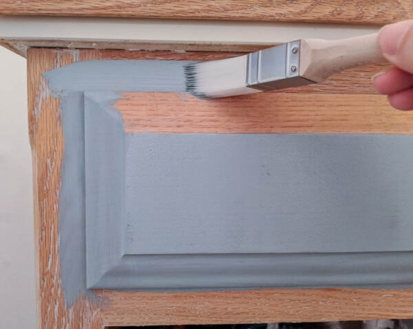 painting an oak vanity light blue using a paintbrush