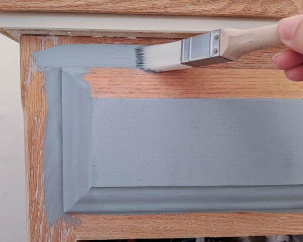 painting an oak vanity light blue using a paintbrush
