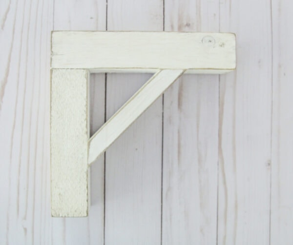 wood shelf brackets with a weathered white paint finish.