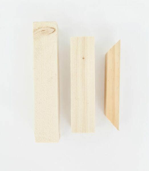 Three pieces of wood needed for diy shelf brackets - two rectangular pieces and a small trapezoid.