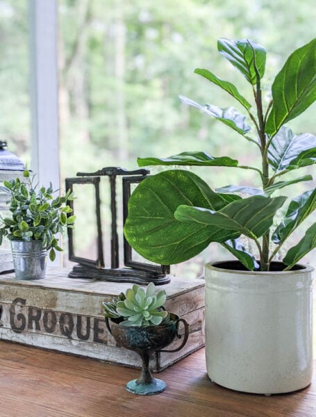 faux fiddle leaf fig and other faux plants on porch
