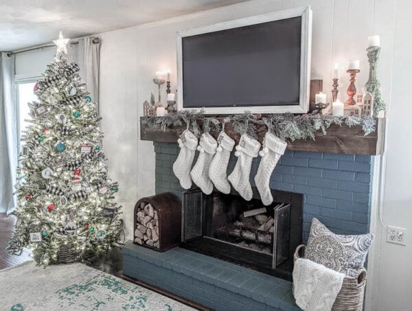 Fireplace with stockings, garland and lit candles next to flocked Christmas tree with white Christmas lights.