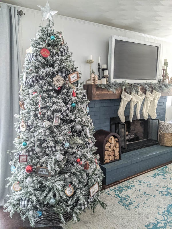 Flocked Christmas tree next to blue fireplace with white knit stockings and garland