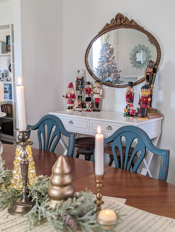 antique gold mirror hanging above white table with nutcracker collection