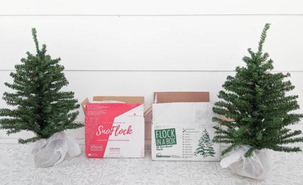 Two mini Christmas trees next to a box of SnoFlock and a box of Sno-Bond Flock in a Box snow flocking powder.