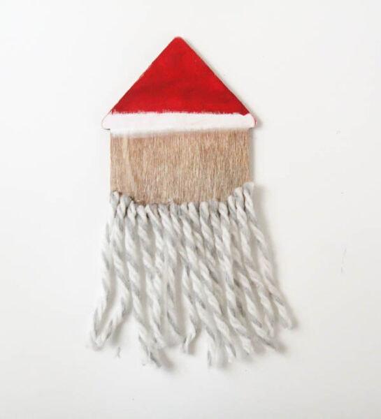 DIY wooden santa ornament with yarn beard glued along bottom.