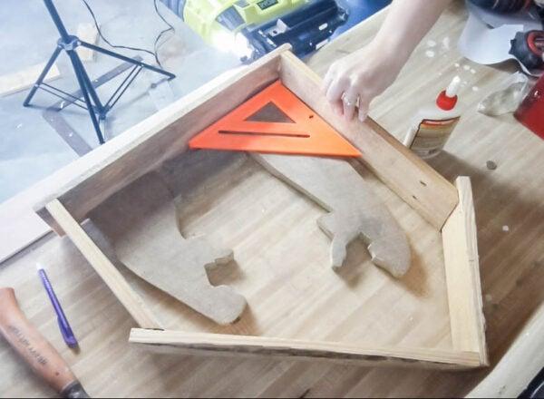 Constructing the wood nativity stable using a nail gun.