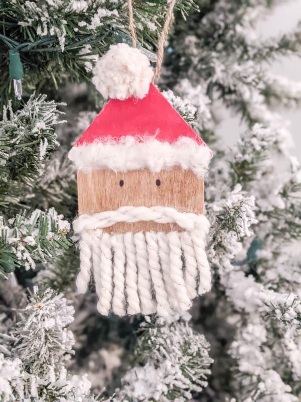 DIY wooden Santa ornament hanging on Christmas tree.
