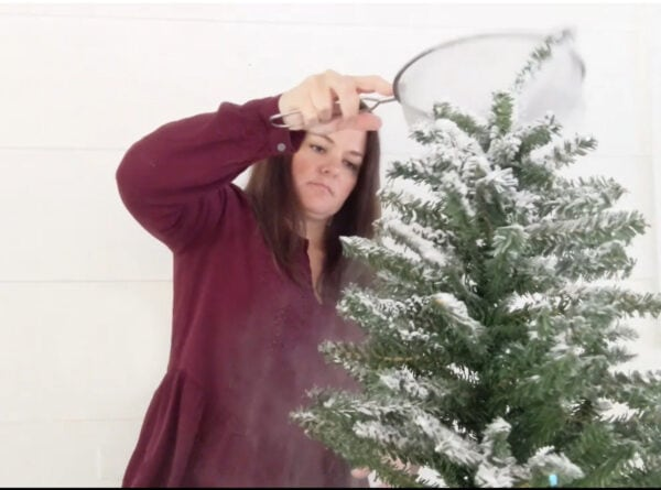 Flocking a small Christmas tree with a wire sifter and flocking powder.