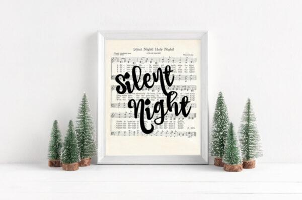 Silent Night Christmas printable in a white frame next to mini Christmas trees