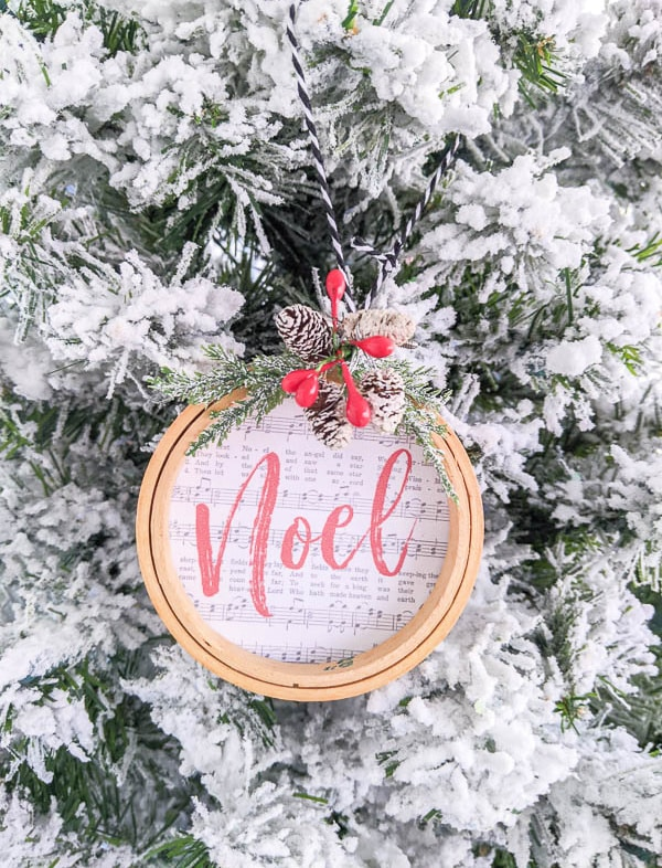 Noel embroidery hoop ornament hanging on flocked Christmas tree.