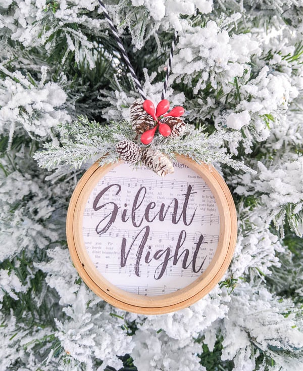 Silent Night embroidery hoop Christmas ornament hanging on flocked Christmas tree.