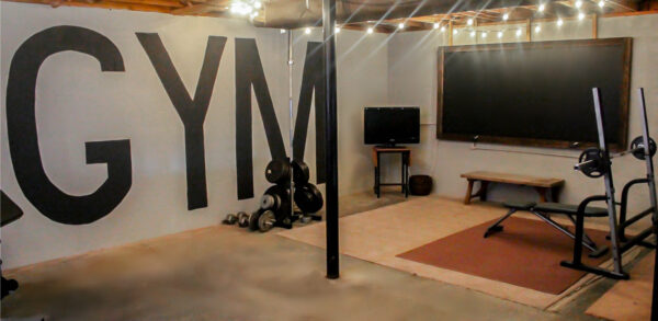 Unfinished basement home gym with gym mural wall and oversized chalkboard