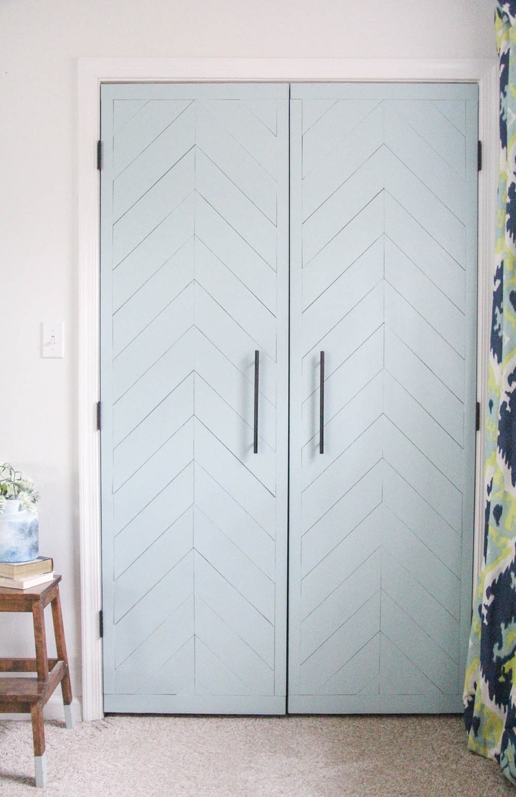 sliding closet door makeover with hinged doors, fresh paint, and a chevron wood pattern.