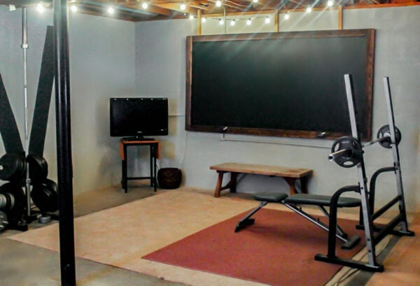 industrial basement gym with free weights, a TV, a rustic bench, and an oversized chalkboard.