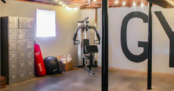 basement gym with large open space, punching bag, lockers, and weight machine.