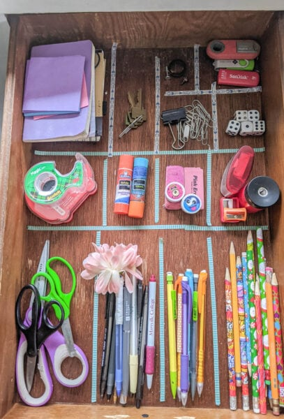 Everything in the junk drawer organized into piles with washi tape marking where the dividers will go.