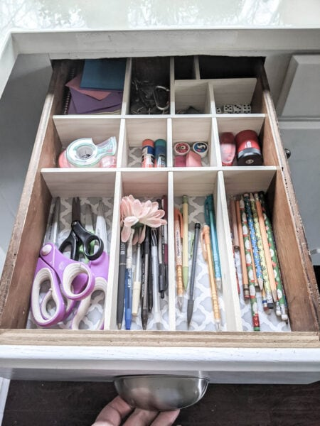 Junk drawer with new DIY wood drawer dividers corralling everything into neat sections.