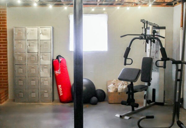 basement gym with punching bag, weights, and lockers.