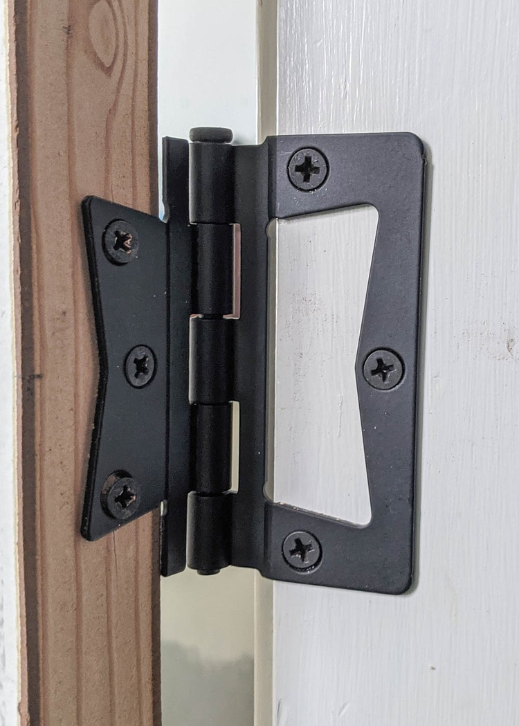 close up of non-mortise hinge attached to door and door frame.