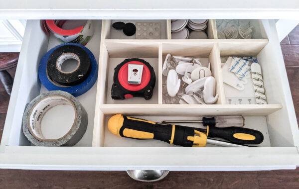 Junk drawer organized with diy drawer dividers with sections for command strips, duct tape, felt furniture pads, a tape measure, and screw drivers.