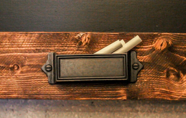 chalk holder on rustic diy chalkboard.