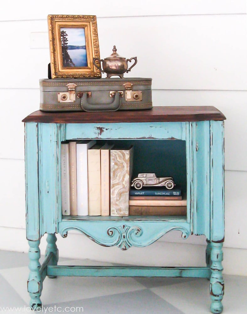 antique radio cabinet painted aqua with a wood top.