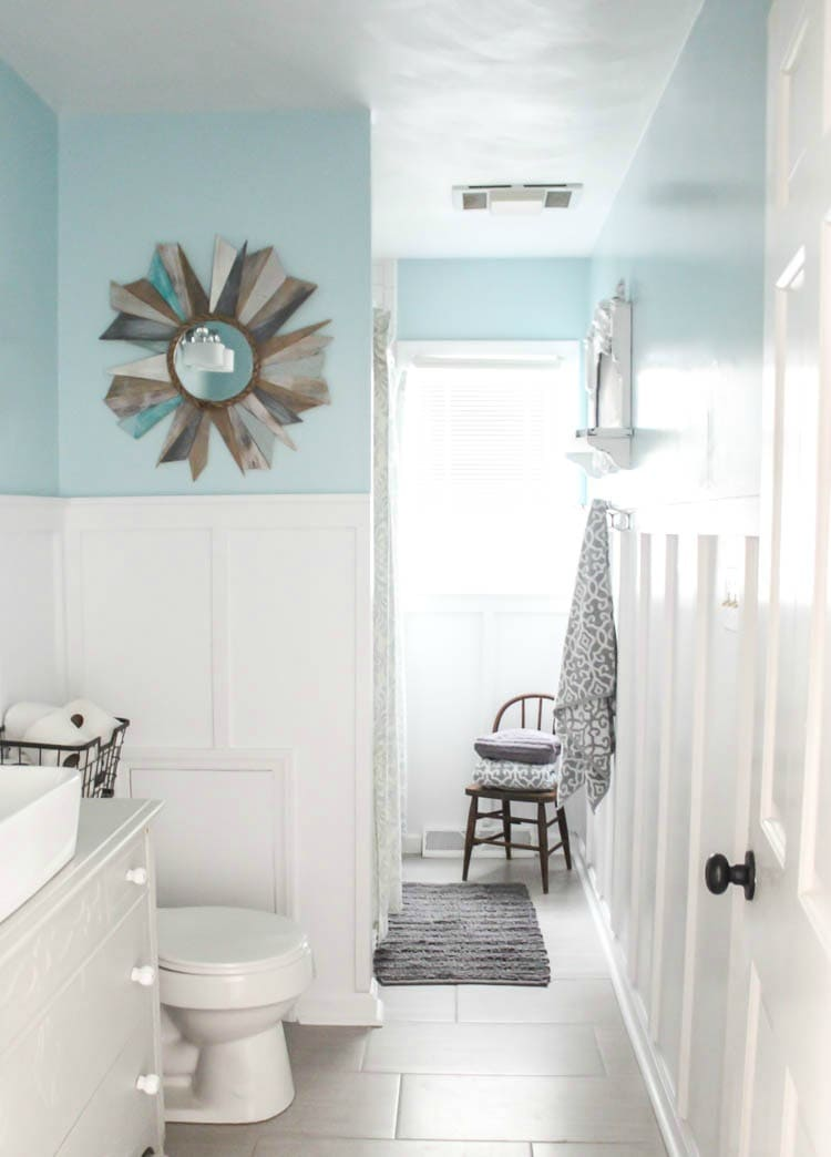 DIY bathroom renovation with board and batten, blue walls, tile floors, and an antique dresser vanity.