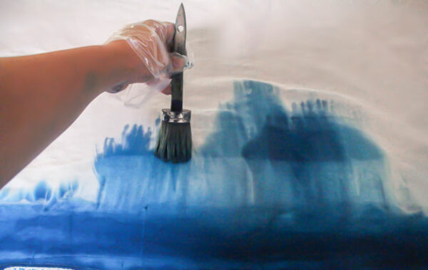 using a paintbrush to make ombre curtains.