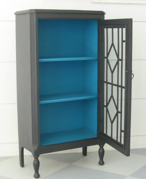 small cabinet painted charcoal gray with a pop of turquoise inside.