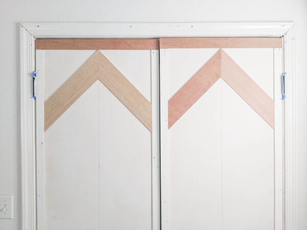 first row of chevron wood planks attached to door.