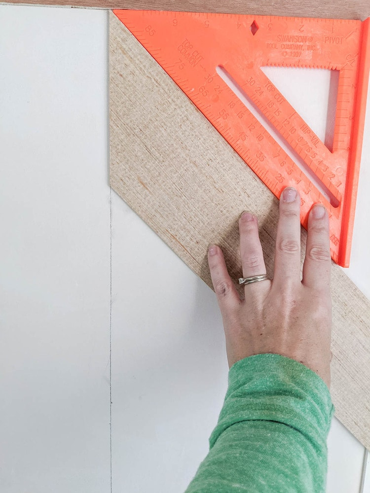 using a speed square to double check the angle on the first wood plank.