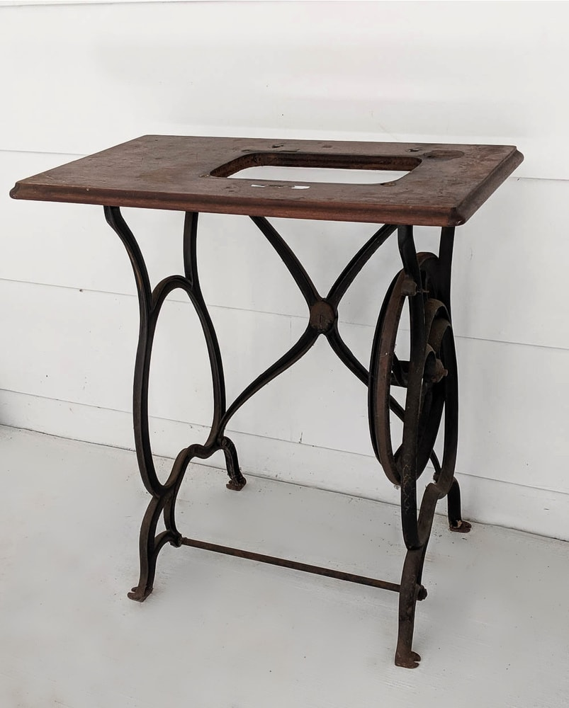 old sewing machine table with iron legs and no sewing machine.