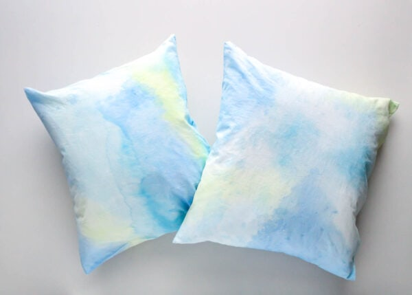 pair of painted pillows with blue and green watercolor abstract painting.