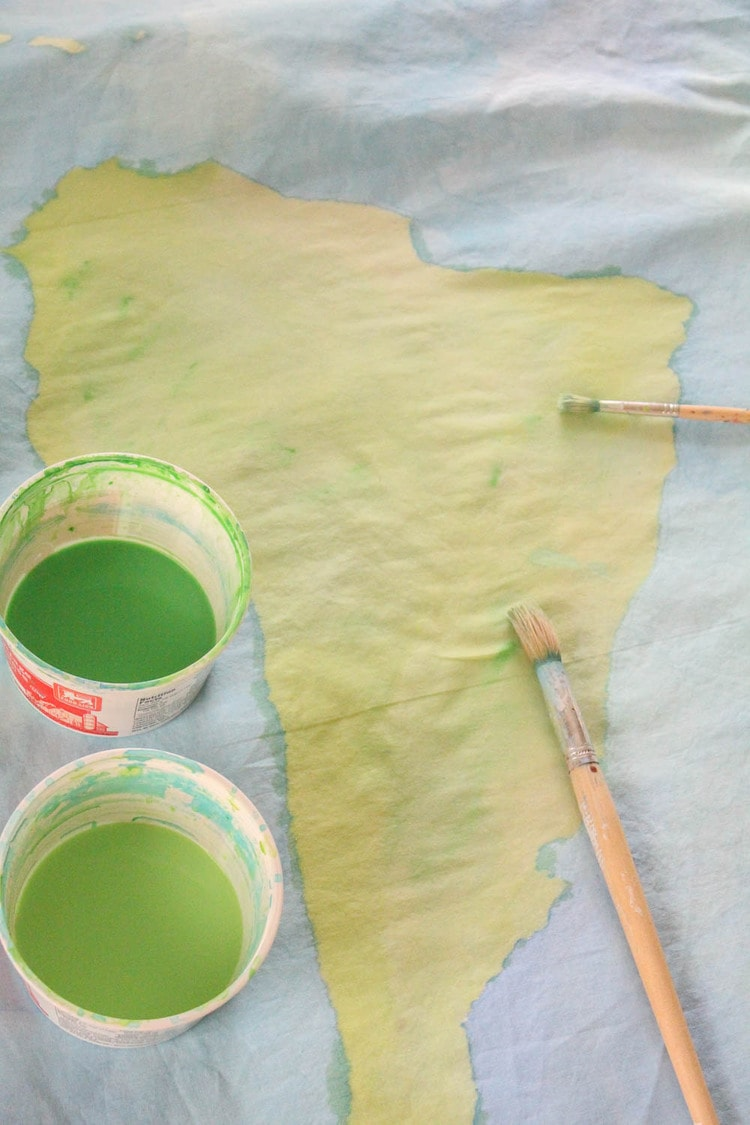 painted outline of Africa on duvet cover with paint brush and cups of green paint.