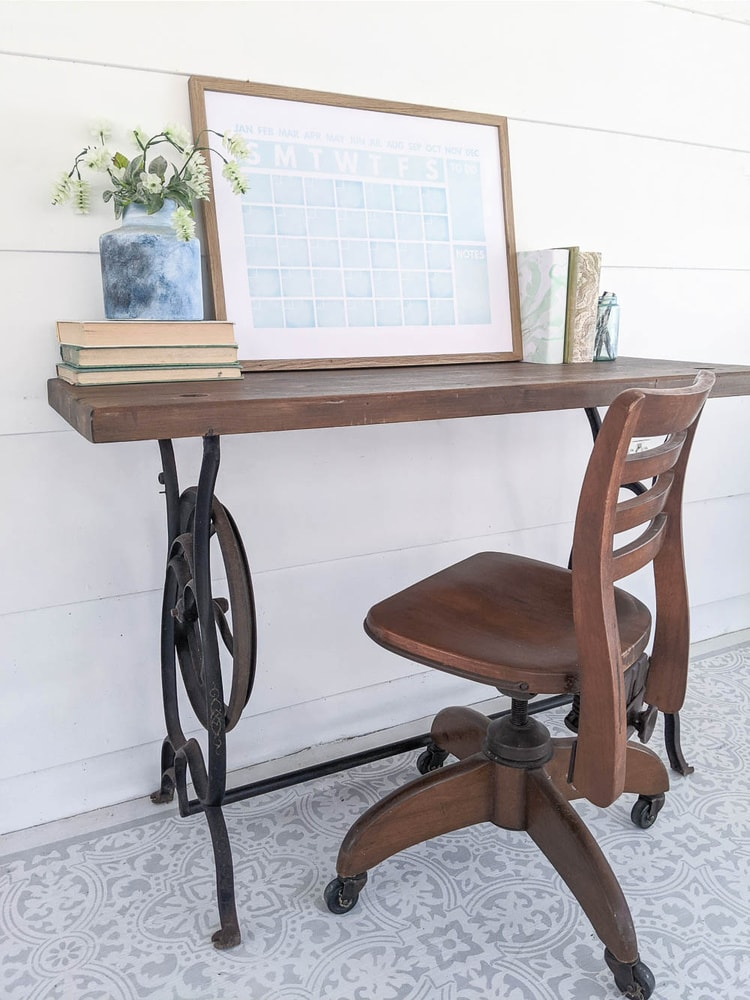 sewing machine table repurposed as a desk with a vintage wooden chair.