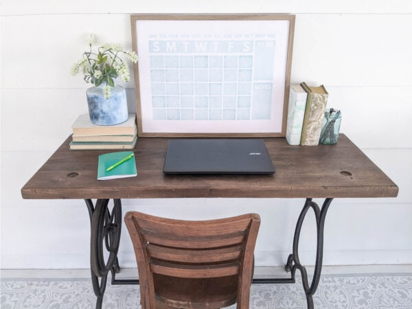 repurposed sewing machine table desk with laptop and pad of paper on top.